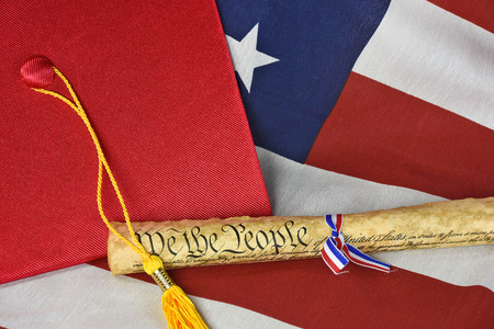 us constitution: graduation cap and gold tassel on flag with old US constitution
