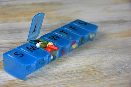 variety of pills in blue plastic pill organizer