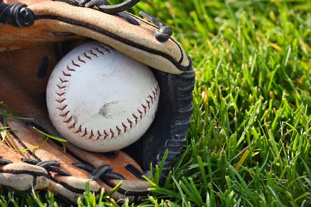 Weiß Softball in abgenutzten Sporthandschuh auf Gras Standard-Bild