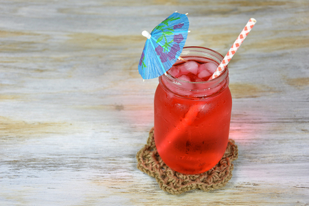 paper umbrella: fruit punch drink with paper umbrella in glass mason jar Stock Photo