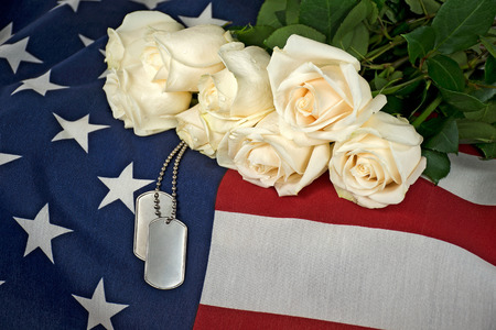 Military dog tags and white rose bouquet on American flag