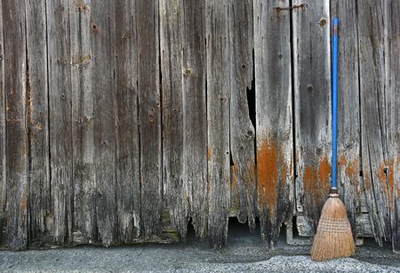 broom handle: old broom with blue handle leaning on barn wood siding