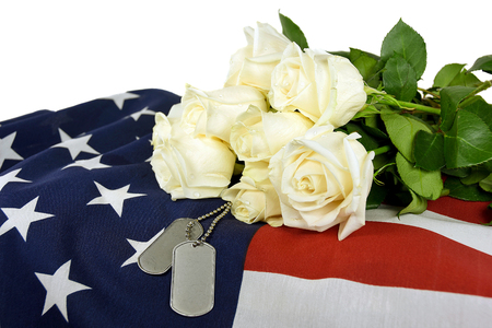 heroism: military dog tags on American flag with white roses