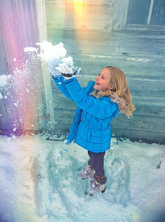 little girl throwing snow in rainbow