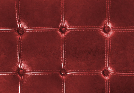 tufted: close up of red tufted leather upholstery with buttons