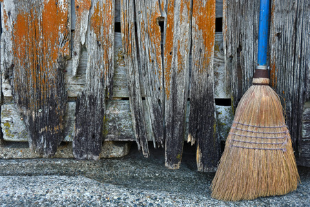 broom handle: old broom with blue handle by dilapidated barn Stock Photo