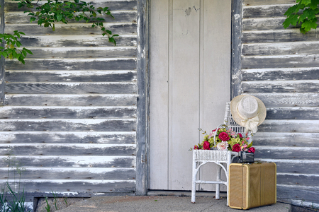 stoop: vintage camera on old suitcase by wooden door