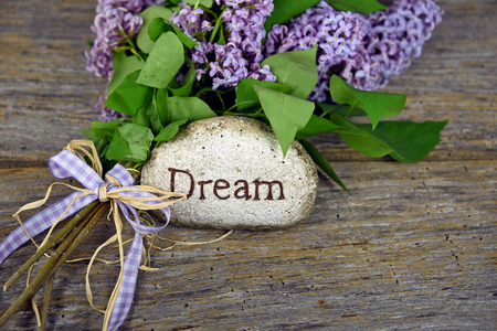 lilac bouquet with dream carved on rock Stock Photo