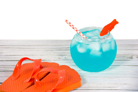 fish bowl: cocktail in fish bowl with orange flip-flops on wood