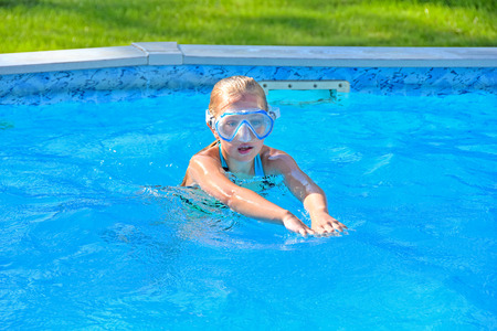 little blond girl in swimming pool with swim goggles Фото со стока