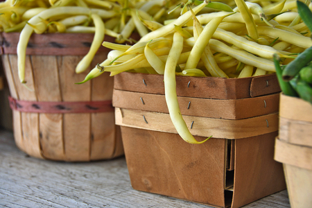 bushel: raw yellow beans in wooden produce box and bushel basket at the market