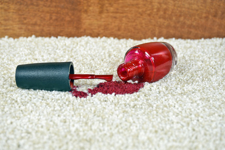 bright red nail polish spilled on light colored carpet Banco de Imagens - 62761311