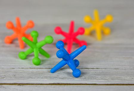jacks: close up of colorful toy jacks on wood Stock Photo