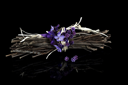 violet bouquet and purple ribbon on twig bunch with black reflection Stock Photo