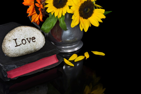 bible flower: word love carved in stone on Holy Bible with sunflower bouquet