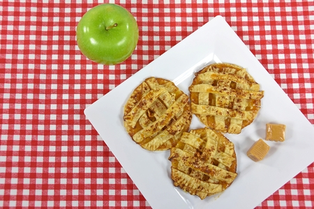 apple pie cookies and caramel candy on white square plate with green apple