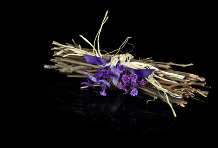 violet bouquet tied to twig bundle with purple satin ribbon on black reflection