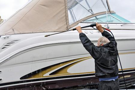 man pressure washing a power boat hull