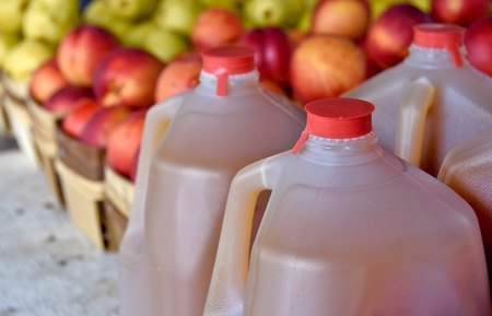 apple cider in gallon jugs with apples at the market