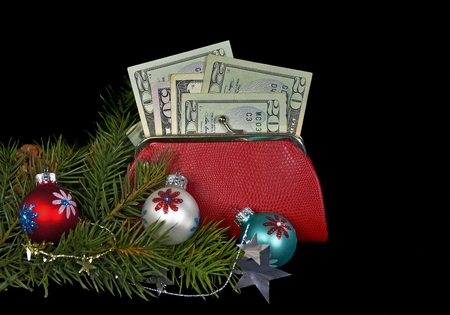 Christmas money in red purse with ornaments on black