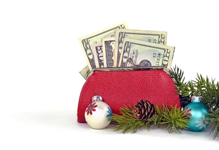 money in red change purse with Christmas ornaments isolated on white