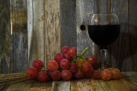 shadowed: red wine and grapes on rustic barn wood Stock Photo