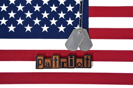 tribute: military dog tags and word patriot in wooden letterpress type on american flag