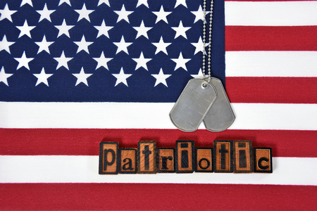 letterpress type: word patriotic in letterpress type and military dog tags on flag