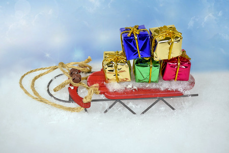 old-fashioned sled with wrapped Christmas gifts in snow