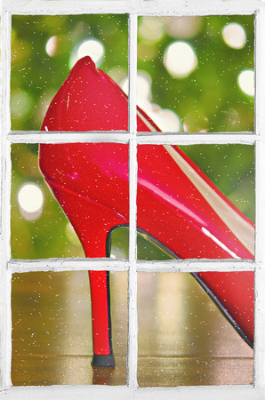 red high heel shoe in windowpane with Christmas lights and snowflakes Stock Photo