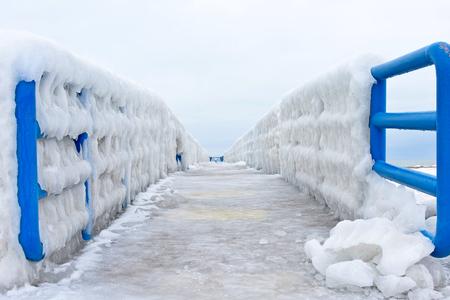 michigan snow: ice formation on blue pier railing in Lake Michigan
