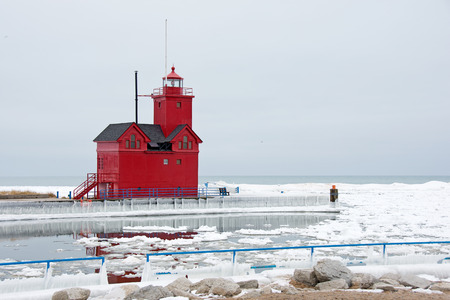 lake michigan lighthouse: red lighthouse on Lake Michigan in winter Foto de archivo