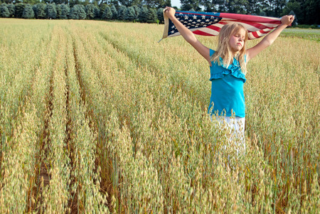 young girl in wheat field with American flag