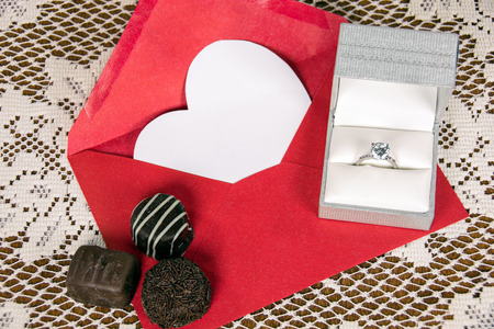 chocolate candy and  diamond ring with white heart in red envelope