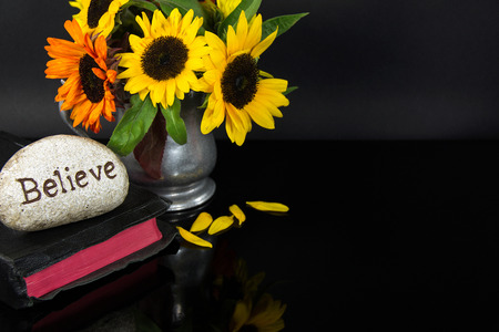 word believe carved in stone on Bible with sunflower bouquet