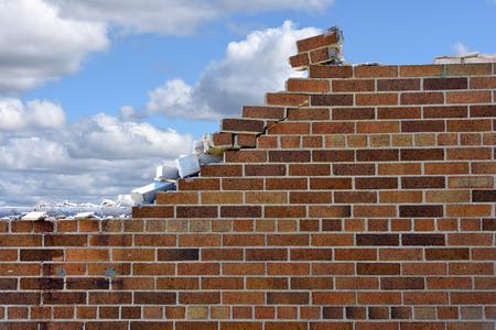 afbrokkelende bakstenen muur met pluizige wolken in blauwe hemel