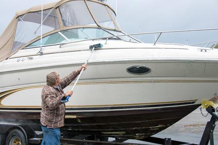 長いブラシで力のボートを洗う人