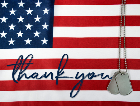 word thank and military dog tags on American flag Stock Photo