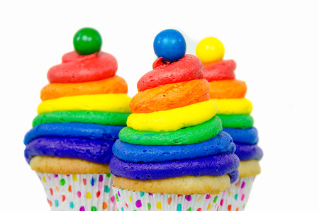 Rainbow swirl frosting and gumball on cupcakes isolated on white Stock Photo