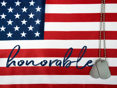 Word honorable on American flag with military dog tags