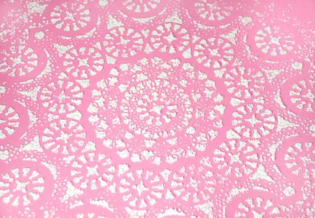ornate powdered sugar design on pink Stock Photo