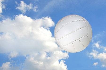 airborne white volleyball with fluffy white cloud background