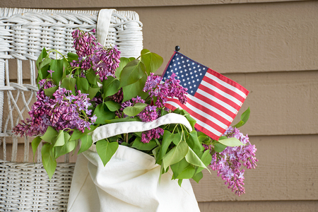 Lilac bouquet with American flag in hanging muslin sack on wicker chair Stock Photo