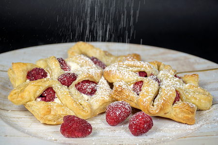 Powdered sugar sprinkle on raspberry pastry on wood plate Stock Photo