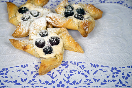 puff pastry pinwheels with blueberries and powdered sugar on lace paper doily