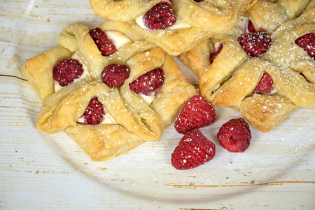 puff pastry with raspberry fruit on woodgrain platter