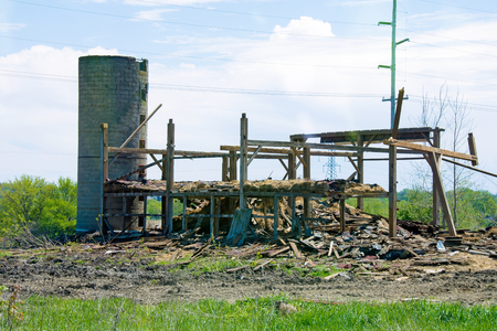 dismantled: old wooden barn with silo being dismantled on farmland Stock Photo