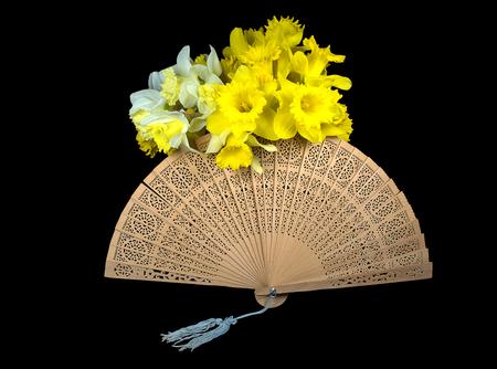 黒に分離されたヴィンテージの木製手ファンの水仙の花束