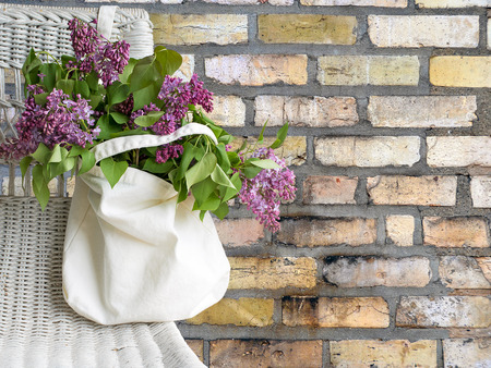 lilac bouquet in muslin sack hanging on wicker chair with brick background