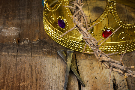 rusty nail: gold crown and crown of thorns with rusty nails on rustic wood Stock Photo